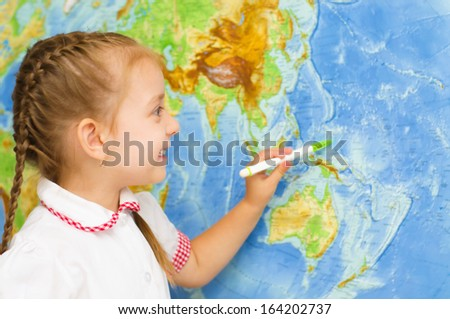 happy little girl smiles by world map - stock photo