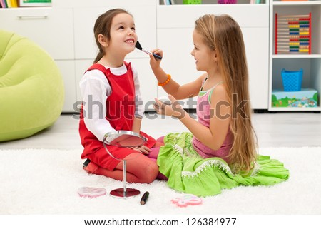 Happy little girl smiling while her face is powdered - stock photo