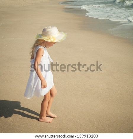 happy little girl standing on beach - stock photo