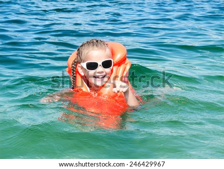 Happy little girl swimming with life jacket in the sea - stock photo