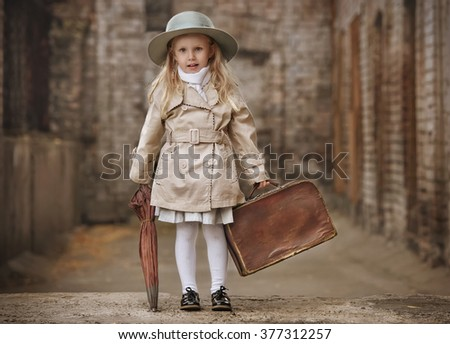 Happy little girl traveling with old suitcase and umbrella at ulitsme old town autumn day - stock photo