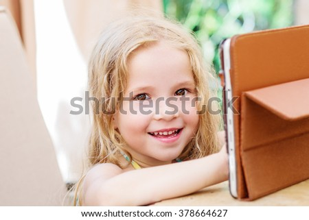 Happy little girl using tablet computer oudoors - stock photo