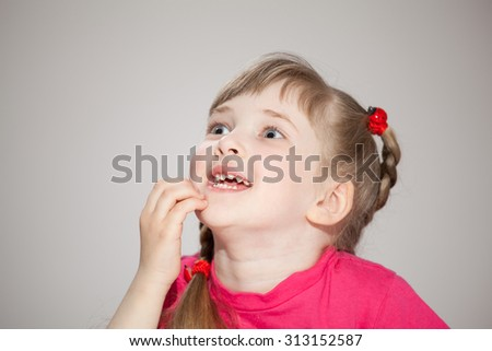 Happy little girl waiting surprise, grey background - stock photo