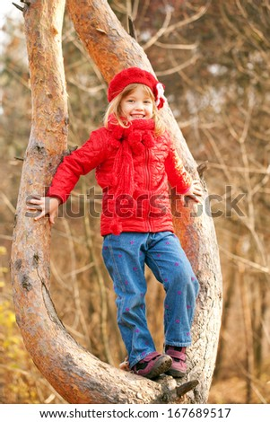 Happy little girl wearing a red sitting in a tree and smiling - stock photo