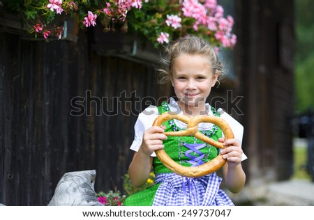 Happy little girl wearing a traditional Bavarian dress dirndl  holding a pretzel in hands during Oktoberfest in Germany  - stock photo