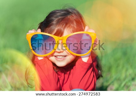 Happy little girl  wearing big sunglasses in the meadow - stock photo