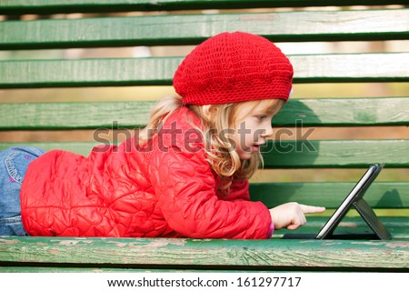 Happy little girl wearing red working with tablet pc and lying on bench in the park. - stock photo