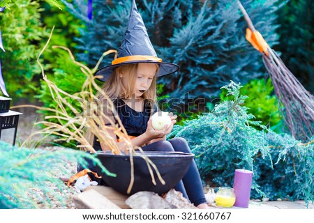 Happy little girl wearing witch costume on Halloween outdoors - stock photo