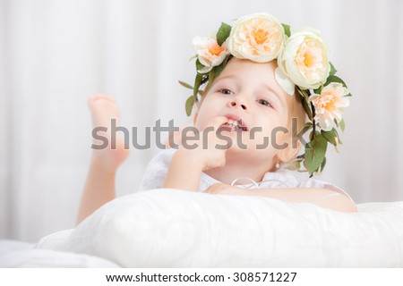 happy little girl with a wreath on the head on a bed - stock photo