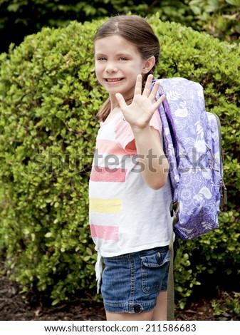 Happy little girl with backpack waving goodbye - stock photo