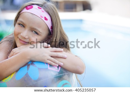Happy little girl with ball by poolside - stock photo