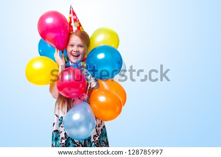 happy little girl with balloons on blue background - stock photo