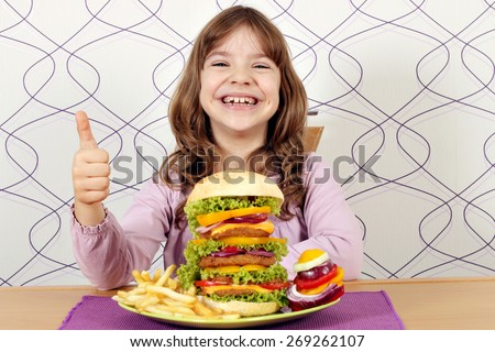 happy little girl with big hamburger and thumb up - stock photo