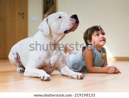 Happy little girl with big white dog lying on the floor at home. Focus on dog  - stock photo
