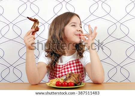 happy little girl with chicken wings and ok hand sign - stock photo