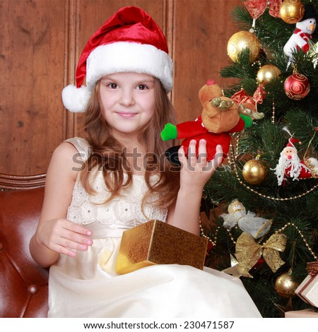 Happy little girl with christmas present smiling - stock photo