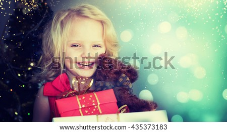 Happy little girl with chrstmas gift - stock photo