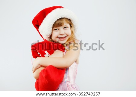 Happy little girl, with curly blond hair, wearing on pink dress, red santa hat, posing with red bag for presents, on white background, in studio, waist up - stock photo