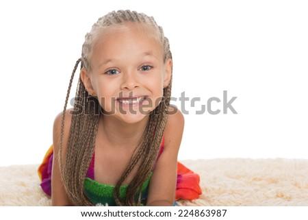 Happy little girl with dreadlocks on the mat. Girl six years. - stock photo