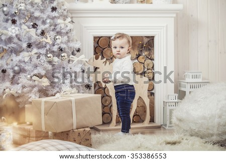 Happy little girl with gifts in beautiful boxes in the Christmas interior - stock photo