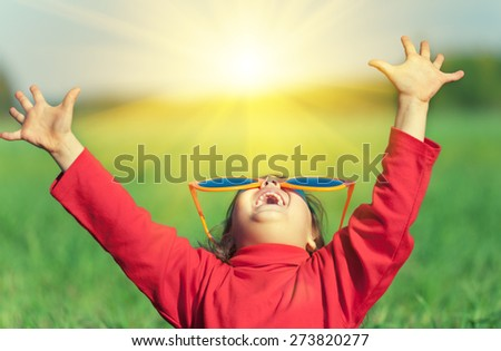 Happy little girl with hands in the air wearing big sunglasses and looking at the sun   - stock photo