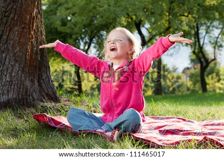 happy little girl with hands up in summer park - stock photo