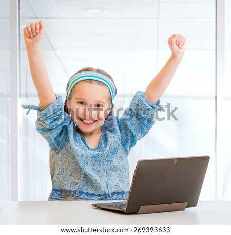 Happy little girl with her  tablet isolated on white - stock photo