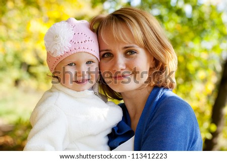 Happy little girl with her young mother - stock photo