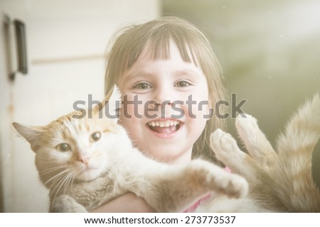 Happy little girl with kitten at home. - stock photo