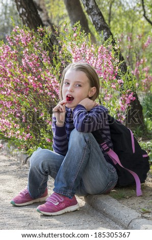 Happy little girl with lollipop outdoors in spring - stock photo