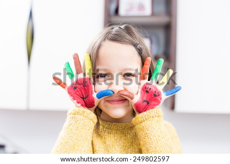 Happy little girl with painted hand - stock photo