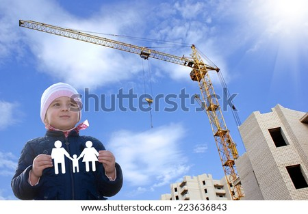 Happy little girl with paper family in hands.Construction new home for young family - stock photo