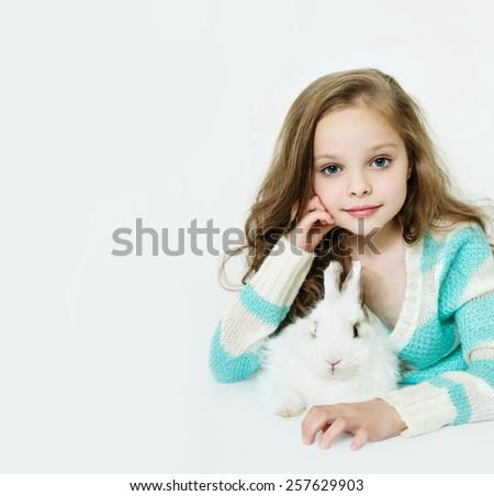 Happy little girl with rabbit - stock photo