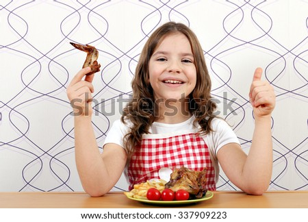 happy little girl with roasted chicken wings and thumb up - stock photo