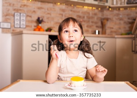 happy little girl with spoon and lemon cake - stock photo