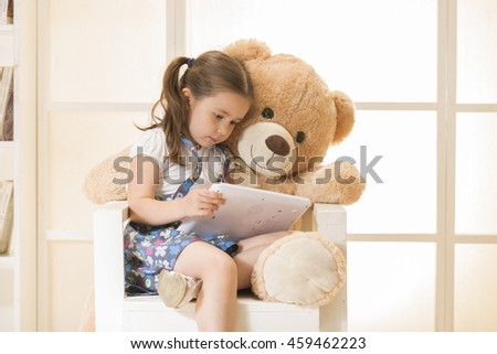 Happy little girl with Teddy bear watching her tablet computer - stock photo