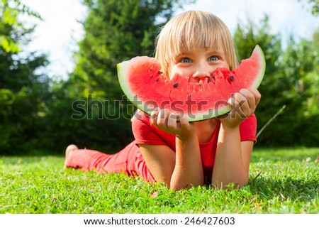 Happy little girl with watermelon in a garden - stock photo