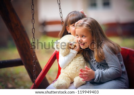 Happy little girlfriends on swing in park - stock photo