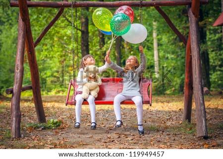 Happy little girlfriends on swing in park - stock photo