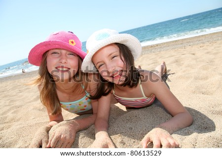 Happy little girls at the beach - stock photo