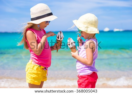 Happy little girls eating ice-cream over summer beach background. People, children, friends and friendship concept - stock photo