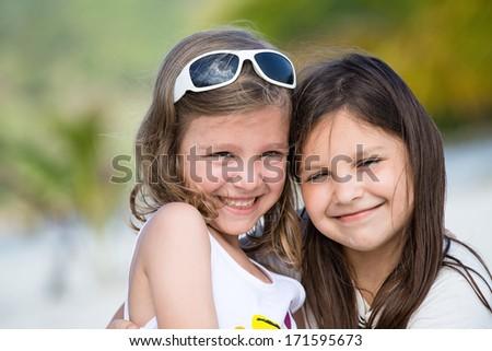 Happy little girls enjoy summer day at the beach - stock photo