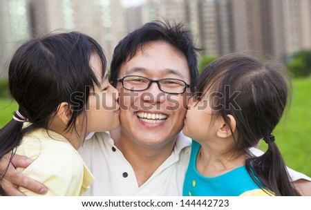 happy little girls kissing their father - stock photo