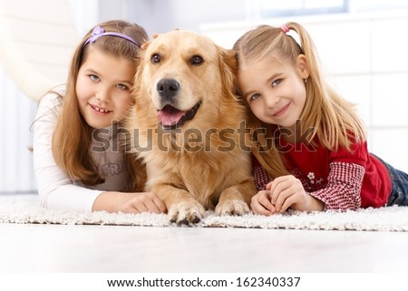 Happy little girls lying prone on floor at home with golden retriever, smiling. - stock photo