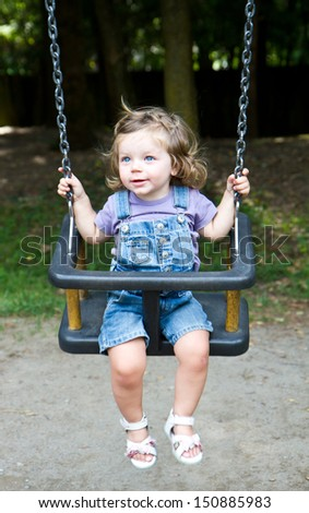 happy little girls  on a swing  - stock photo