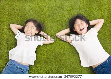 happy Little  girls resting on the grass - stock photo