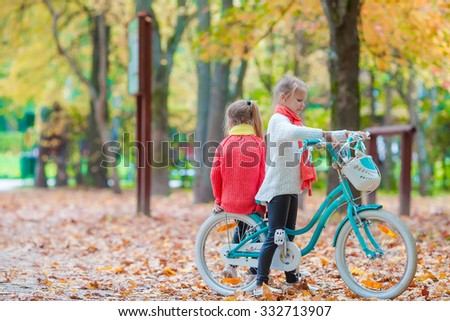 happy little girls riding a bike at beautiful autumn day outdoors - stock photo