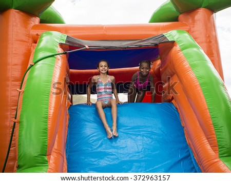 Happy little girls sliding down an inflatable bounce house  - stock photo