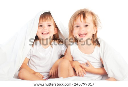 happy little girls twins sister in bed under the blanket having fun, smiling - stock photo