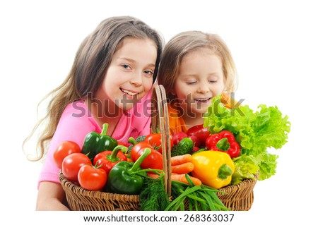 Happy little girls with basket of vegetables - stock photo